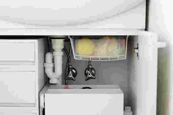 洗面台下のパイプや水栓がある部分は収納が難しい部分ですね。つっぱり棒を使えば、そんなデッドスペースも有効活用できます。こちらでは吊り下げワイヤーバスケットをつっぱり棒に引っかけて使っています。