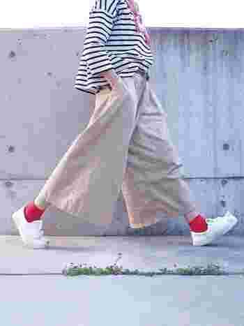 シンプルなモノトーンボーダーコーデは、カラフルな靴下を差し色として加えるのもおすすめ。クロップド丈のワイドパンツに赤の靴下を合わせ、さらに白スニーカーで春らしい足元を作っています。