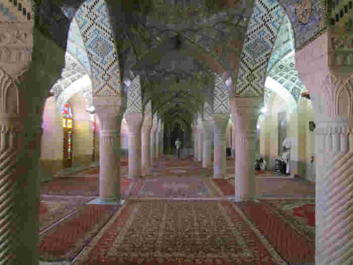 ピンク色が特徴の植物文様が施された、シーラーズ(イラン)にある伝統的なマスジェデ・ナスィーロル・モスク!ステンドグラスから差し込む朝日によって、さまざまな光のアートを創りだします。まるで万華鏡の中にいるみたいですね。