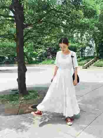オールホワイトのロングスカートのコーディネイト。きゅっとまとめたストレートヘアが、ふわりと優しいロングスカートを甘くなりすぎずに見せてくれます。赤いスニーカーでカジュアルダウン◎。