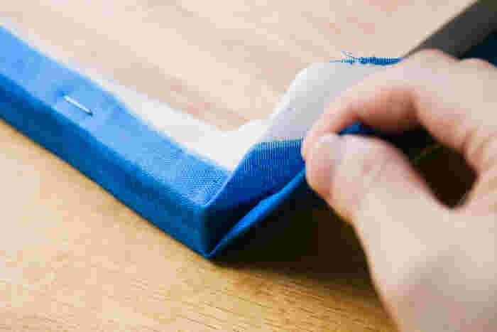 写真のようにパネルの角に沿って布をきっちりと折りこみ、軽く引っぱりながらガンタッカーでとめます。角をとめたら、残りの辺をとめます。