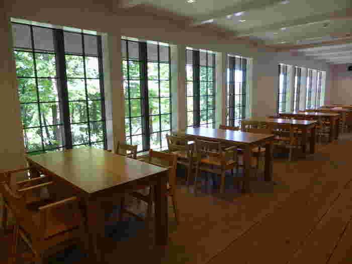 白い壁にパインの床。家具は富山市粟巣野(あわすの)の家具製作所「KAKI」によるもの。 余分なくシンプルな室内には、お料理も、外の緑も映えます。