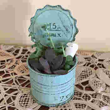 こちらはブリキ缶にミルクペイントを施した花器です。多肉植物の寄せ植えの中にある、かわいい陶器の人形がポイントになっています。