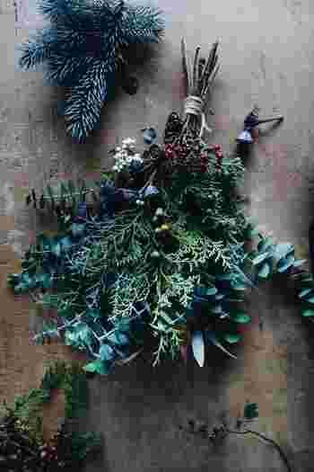 """オシャレな雑誌で見かけるような""""ナチュラルクリスマス""""に憧れているという方におすすめなのがこちら。東京の中目黒と蔵前に小さな店を構える、花と緑の小さな専門店「ex.(イクス)」のクリスマススワッグです。  草や実、枝などを使って丁寧に作られたスワッグは、ドライではなくフレッシュな素材を使用。飾っている間に、少しずつドライになっていく様を楽しめますし、クリスマス後もシーズンを通して飾ることができます。"""