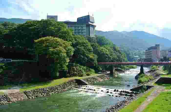 「箱根湯本」は、箱根町の東部に位置し、箱根湯本駅周辺から、湯坂山の山麓に流れる早川(はやかわ)と須雲川(すくもがわ)に沿って東西に細長く広がる町です。西部は緑深い山々が連なるため、実際の町は、東部の箱根湯本駅周辺、両川沿いに集中しています。  【早川と箱根湯本界隈(正面に架かる赤い橋は、箱根湯本駅傍の「あじさい橋」。正面は、三島方向。連なる山並みの向こう側に芦ノ湖がある。)】