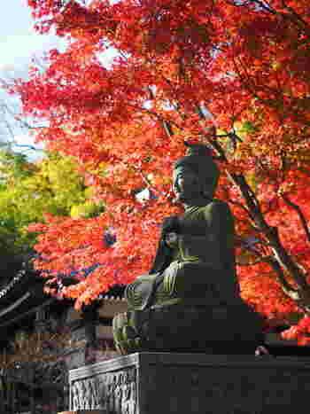 燃えるような紅葉を背にした仏像。