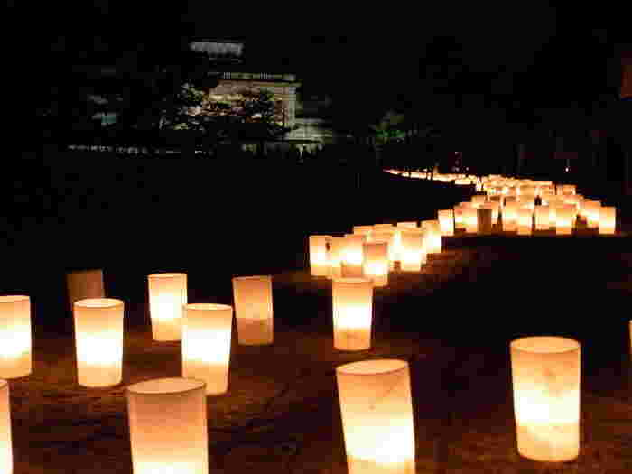 奈良公園に隣接する奈良国立博物館の敷地内には、奈良で最初の本格的洋風建築、旧帝国奈良博物館本館だった「なら仏像館」があります。明治の香り漂うどっしりした洋館がライトアップされている様子もとてもカッコいいのですが、その周囲にもたくさんのろうそくが並んで光の帯を作っています。