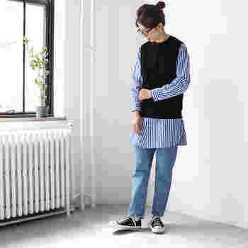 黒のニットベストに、濃い青のストライプシャツを合わせた着こなし。ボトムスもブルーのデニムをチョイスして、全体を同系色でまとめています。足元はスニーカーで、シャツのかっちり感を上手にカジュアルダウン。ナチュラルなデイリーコーデの完成です。