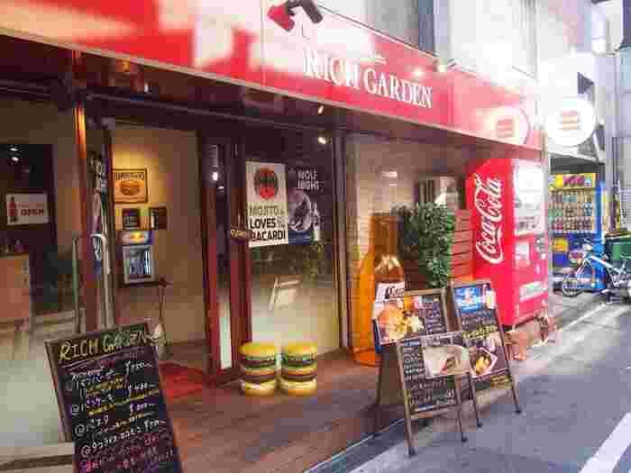アメリカ村の中心から少し離れた場所に位置する「RICH GARDEN(リッチガーデン)」。ログハウスのような木目と赤い看板が目を引くハンバーガーショップです。看板のハンバーガーマークがなんともかわいらしい!