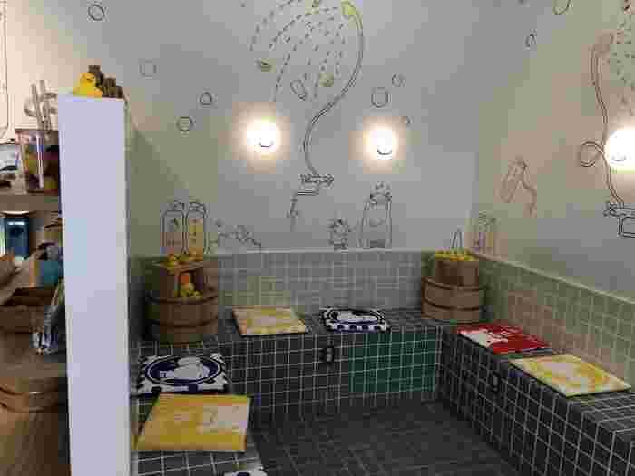 駅から徒歩10分ほどのところにある「熱海プリン カフェ2nd (カフェセカンド)」は、熱海銀座商店街でひときわ長い行列ができる人気店。店内は、温泉地にちなんでタイル張りの浴槽や風呂桶が置かれていてユニークな印象です。
