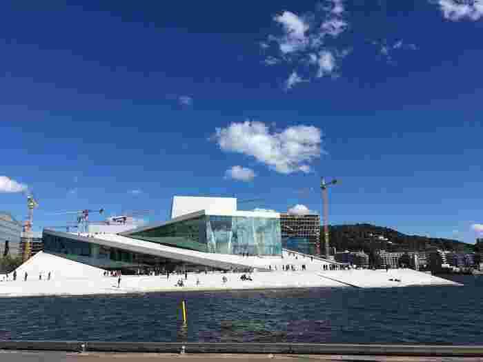 """""""ノルウェーの自然はみんなのもの""""をコンセプトに2008年にオープンした、ノルウェー・オスロのシンボルの一つ「オペラハウス(Operahuset)」は、オスロを訪れたら必ず訪れていただきたい場所。海の上にポツンと浮かぶ、真っ白な建築は一際目を引きます。屋根の上へは誰でも登ることができ、海側からオスロの美しい景色を鑑賞することができます。"""