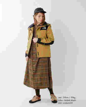チェック柄のシャツワンピースにマウンテンパーカーを羽織った山ガール風コーデ。ブラウンやマスタードなど秋色がおしゃれです。キャップを被ってスポーティーさをプラス。