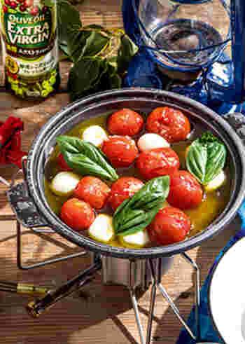 """こちらは、プチトマトとモッツァレラチーズ、バジルの葉を使用したアヒージョ。  バゲットにのせていただけば、ピザの""""マルゲリータ""""のような楽しみ方ができますよ*。見た目も鮮やかで、ホームパーティーにもぴったり。余ったらパスタにあえたりしても美味しそうですね。"""