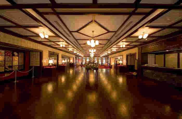これぞ非日常!な大正ロマン溢れる内装で大人気の金沢白鳥路ホテル山楽のロビー。クラシカルな板張りの床に真紅の絨毯、格子天井から吊り下げられたレトロな照明はまるで鹿鳴館のよう。