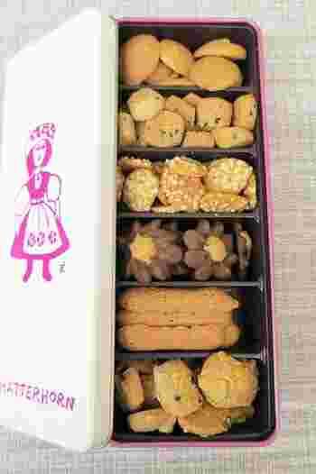 お店のパッケージは、鈴木信太郎画伯の絵がデザインされています。「缶入りクッキー」は、白地にピンクの女性のイラストが映える、クラシカルなデザイン。  缶を開けるとミニサイズのクッキーがギュッと詰め込まれていて、どれを食べよう…というワクワクしてきます。サイズは5つまで展開しており、お取り寄せも可能です。