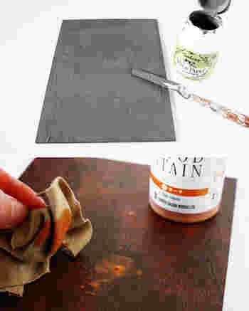 台紙を水性塗料でアンティーク風にペイントします。筆の代わりに、ペインティングナイフなどを使って凸凹感を出すのがおすすめ。味わいのある表情になりますよ!  スポンジで叩き塗りした後に水性のウッドステインを付着させると、より赤錆っぽい質感に…。