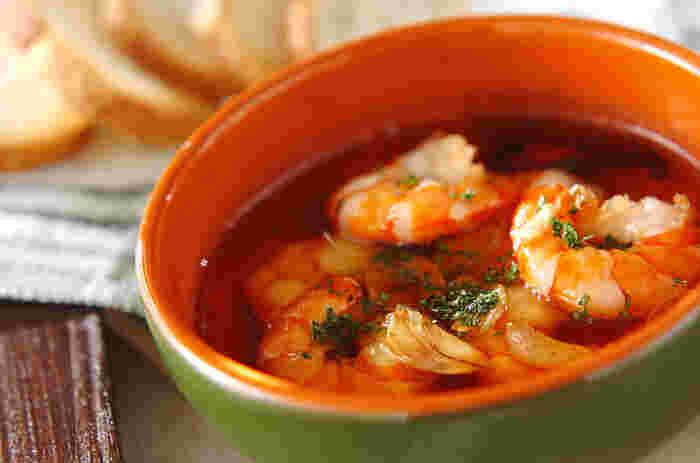 「パエリア」と一緒に食卓に出したい「アヒージョ」は、オリーブオイルとニンニクで煮込む小皿料理。こちらはエビのレシピです。キノコ類や野菜、チキンなどでも美味しいですよ。ニンニクの風味がくせになる味わいです。バゲットを浸して食べるのもおすすめ。