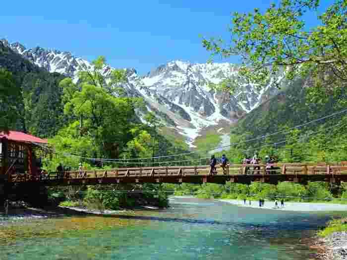 """標高約1,500mの山岳景勝地として知られる「上高地」。清流""""梓川""""、梓川にかかる河童橋から望む山なみ、大正池や明神池、徳沢など、「上高地」には、とにかく絶景と呼ばれる美しい風景が沢山あります。 その手付かずの美しい自然は、国の「特別名勝」と「特別天然記念物」に指定され、別名「神の降り立つ地(神降地)」とも称され、毎年150万人もの人々が訪れる日本屈指の観光スポットです。"""