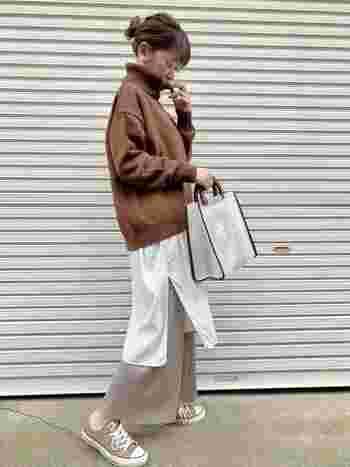 ブラウンのオフタートルニットに、白のシャツワンピースをレイヤードした着こなしです。ワンピースの下にはベージュのワイドパンツを重ねて、こなれ感たっぷりなナチュラルコーデに仕上げています。足元はワイドパンツと色を揃えたスニーカーで、カジュアルな印象に。パンプスやブーツに変えれば、フェミニンな雰囲気でも着こなせます。