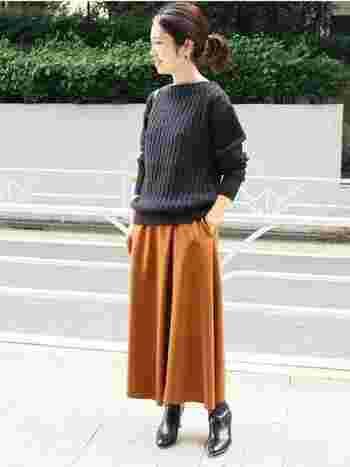 シンプルなリブニットにテラコッタのロングスカートを合わせたコーデ。光沢のある質感が上品で、レザーブーツとも好相性です◎