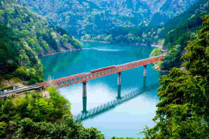 周囲に民家が無く、切り立った断崖と湖に浮かぶ独特の風貌を持つ奥大井湖上駅は、「陸の孤島」のような立地にあることから秘境駅とも呼ばれています。陽射しを浴びてエメラルドグリーンに輝く接岨湖(せっそこ)の湖面、駅と陸地を結ぶ赤い橋、雄大な峡谷が織りなす景色は絶景そのものです。