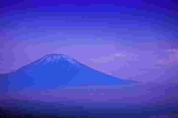 薄紫の空に包まれた梅雨時期の富士山。見たいと思って辛抱強く待った人だけが見られる格別の景色です。
