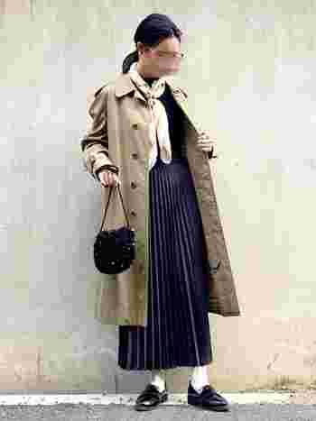 大きめのスカーフにプリーツスカートでクラシカルなコーデに。肌をあまりみせない長め丈×白靴下が上品ですね。
