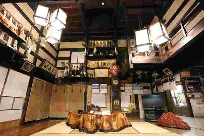 長寿館の中に入ると、神棚などが飾られた趣のある玄関が出迎えてくれます。この玄関は吹き抜けになっていて、解放感があります。また、この玄関の先にある囲炉裏では、ゆっくりくつろいだり、他の観光客と触れ合ったりすることができます。