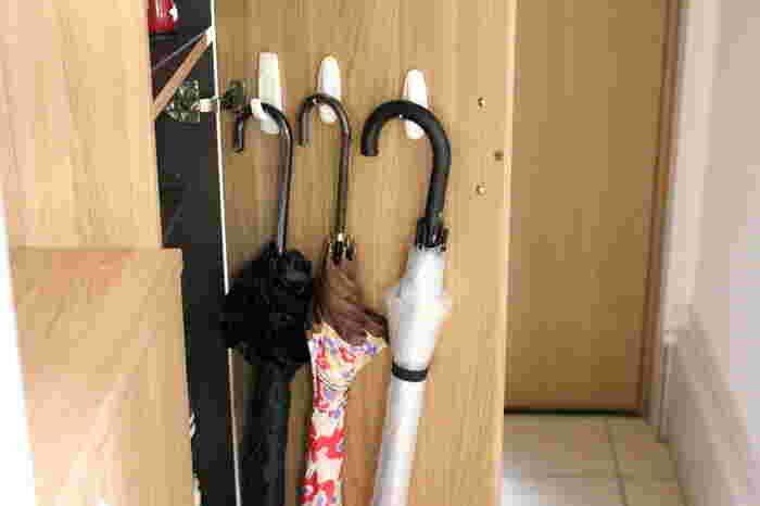 傘は、収納に場所を取ってしまったり、開いた傘を取り出すのに手間取ったりしてしまいがち。そこで、傘にも掛ける収納を取り入れるのがおすすめです。  下駄箱の扉にフックを取り付ければ「隠す収納」に。しっかりと乾かしてから収納すれば、下駄箱の中が濡れることもありません。