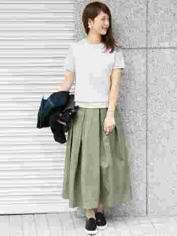 カーキのタックロングスカートを白のトップスできれいめに。スカートのボリューム感が、ふんわりとしたかわいらしさを演出します。