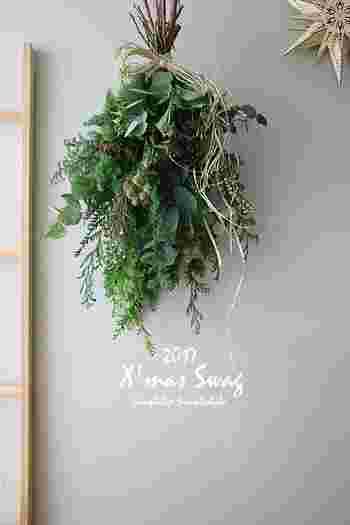 リースよりもさらにシンプルに、グリーンや花を紐で束ね、吊るしたものが「スワッグ」。たくさんの種類をバランスよく束ねるにはコツがあるんです。「軸を揃える」「リボンはたっぷり」お忘れなく!