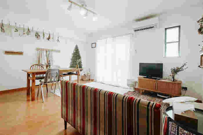 窓に対して横長のLDKの中央にダイニングテーブルを。下に収納スペースがあるダイニングテーブルはunicoのもの。リモコンやティッシュなど、ちょっとしたモノが置けるので便利ですね。ダイニングテーブルからは、テレビやキッチン、壁のおしゃれな飾りなど、お部屋全体が自然と見渡せる配置となっています。