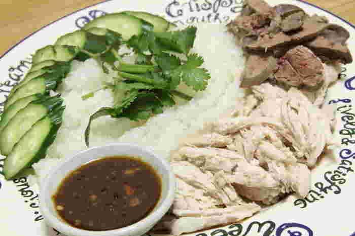 """カオマンガイとは、タイ米(ジャスミンライス)を鶏の油で炒め、鶏のスープで炊き込んだご飯の上に、ゆで鶏(蒸し鶏)のぶつ切りをのせた料理で、甘辛いタレをつけて食べます。""""カオ""""は米、""""マン""""は油、""""ガイ""""は鶏の意味。"""