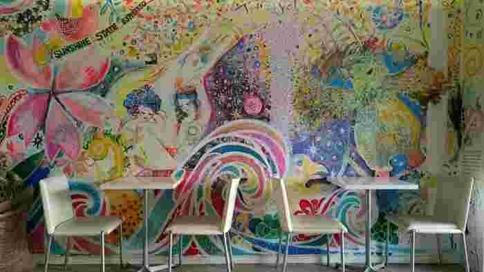 パステルカラーのイラストが描かれたアートな雰囲気の店内は、テーブル席とカウンター、外にはテラス席があります。