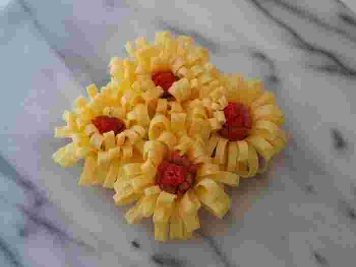 【薄焼き玉子のお花】 先ほどのハムのお花同様、薄焼き卵に切り込みを入れ、中央にウィンナーのお花の中心部分を応用すれば色鮮やかな2色のお花が完成します♪