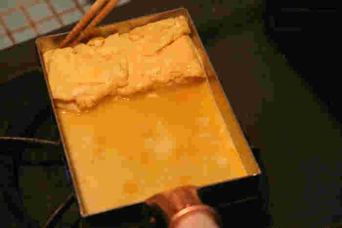 2:熱した卵焼き器に薄く油をしき、卵液の1/4を流しいれます。すぐ菜箸で混ぜ、半熟状態に固まったら手前に向かって折りたたみます。
