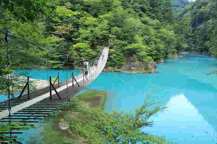 水面があざやかなエメラルドグリーンに輝くのは、水中の微粒子が光に反射する「チンダル現象」が起きるためだといわれます。橋の真ん中で恋愛成就を祈ると叶うともいわれるロマンティックな吊り橋です。
