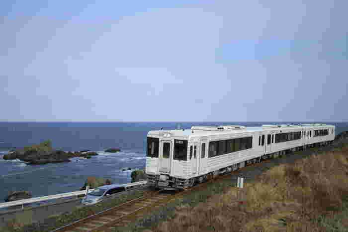 「TOHOKU EMOTION」は、デザイン・食・アートを通して新しい東北を発見・体験する旅をコンセプトにしたJR東日本の「東北レストラン鉄道」です。青森県の八戸駅と岩手県の久慈駅の間の三陸の海沿いを行く列車。白いレンガ造りを思わせる外観が海や空の青に映え、列車というよりレトロモダンな建物が線路を走っているかのよう。