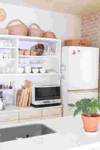 白と木のナチュラルな色でまとまめられたキッチン。かごやトレイの色合いが白のキッチンのアクセントになっていますね。