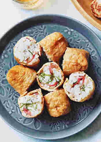 さっぱりした風味の香味野菜を使った一口サイズのいなり寿司。俵型のいなりを半分に切ると、みょうがや大葉のすがすがしい色が顔をのぞかせます。