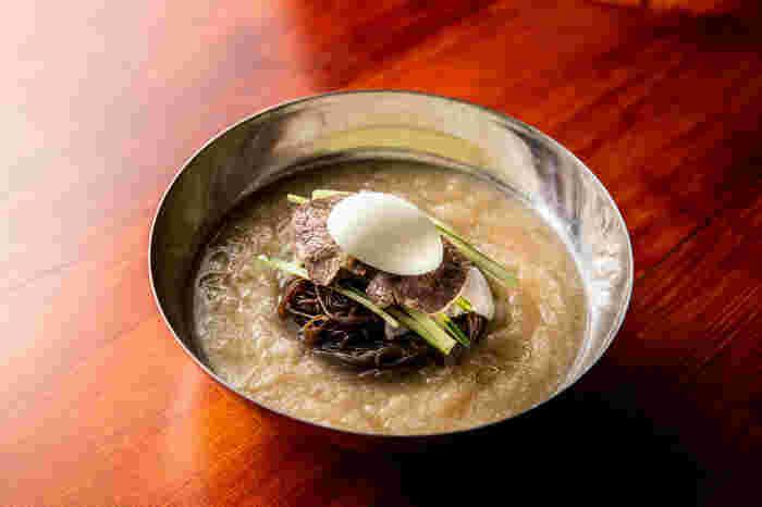 看板メニューは「葛冷麺」。そば粉と葛粉をミックスした黒い麺は、つるつるもちもちでコシがあります。スープはシャーベット状でシャリシャリと冷たく、特製の旨辛タレを加えると、味の変化も楽しめますよ。