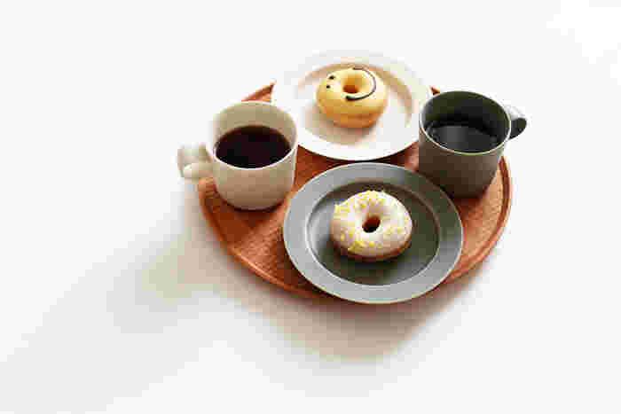 やわらかな感じの彫り模様がとても美しい丸盆。お皿とカップの合間から彫りの陰影がちらりと見えて素敵です。使い込むほどに飴色に変わっていく経年変化を楽しめるお盆です。
