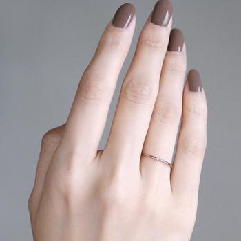 一粒ダイヤモンドが光る華奢なデザインのリングは、女性らしさを引き立てます。落ち着きのあるスモーキーブラウンのネイルが、大人の色気を漂わせていますね。