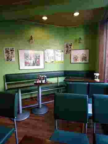 店内には、グリーンの壁紙と椅子が配置されています。通りの賑わいから離れた落ち着いた空間で、ほっと一息つきましょう。