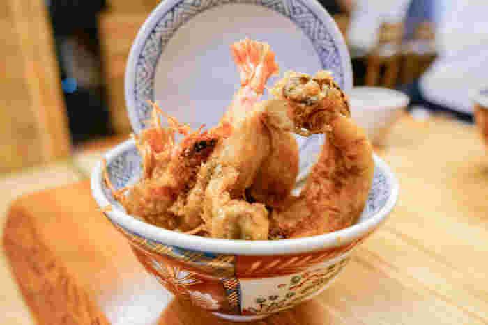 こちらが「まさる」の看板メニュー「江戸前天丼」。頭付きの車海老・穴子・キス・メゴチなどの天ぷらがどんぶりから大胆に飛び出し、絶妙なバランスでふたが立てられています。ごま油が香るサクサクの食感で、一度食べるとまたすぐに食べに行きたくなりますよ!