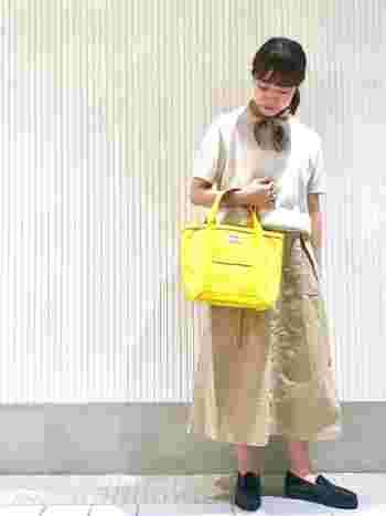 カジュアルなボックスプリーツスカート。縫った後に洗うことでできる「パッカリング」と呼ばれるシワが味を出しています。 ベーシックなコーデには鮮やかなイエローのバッグで差し色を。首元のスカーフもアクセントになっています。