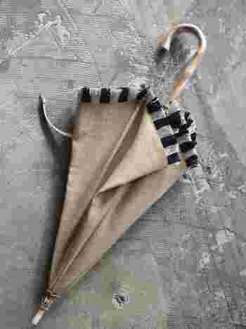 白黒のフリンジがアクセントになった、エレガントな日傘。ベージュは服の色を選ばず使いやすいですね。パンツスタイルにも、スカートにも合うのがgood!