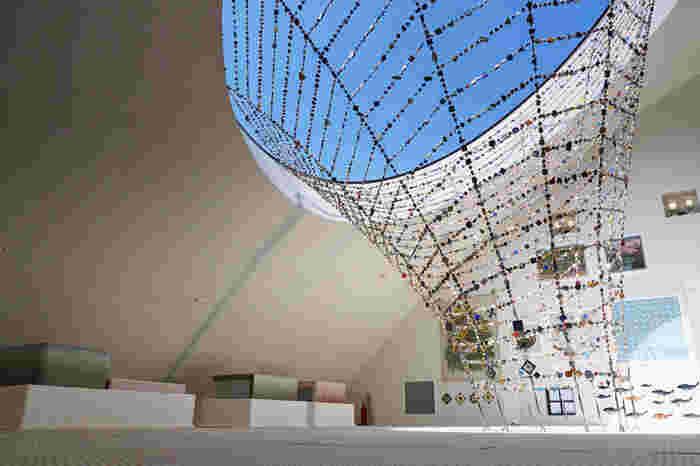 館内には吹き抜けが作られ、明るく開放的な雰囲気です。空へと蜘蛛の巣ように貼られたワイヤーオブジェはモザイクタイルミュージアムを印象付ける空間を作っています。