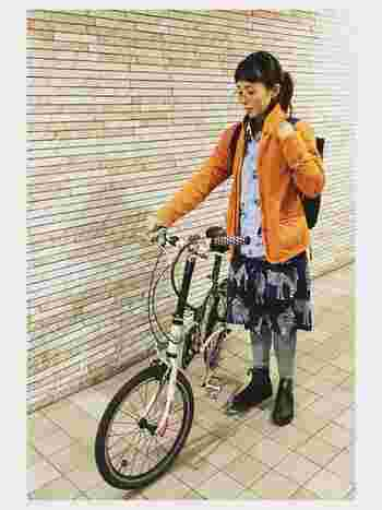 秋冬の街をカラフルに彩るオレンジのジャケットに、アニマル柄のスカートを合わせた遊び心たっぷりのコーデ。インナーにはシャツを、そしてスカートの下にはグレーのレギンスを合わせれば、防寒対策にもなり、自転車のペダルを漕ぐ時にスカートがまくれてしまっても気になりません。足元は黒ブーツで引き締めて。