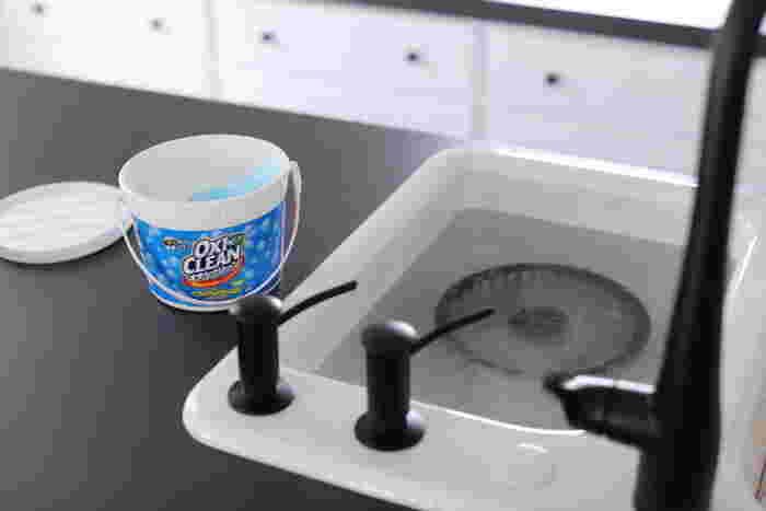 なかなか落ちないガンコな油汚れには、オキシクリーンやアルカリウォッシュを使った「つけ置き洗い」も効果的です。こんなふうに分解した換気扇のパーツをお湯に浸して、オキシクリーンを振りかけておくだけで油汚れを落としやすくなります。